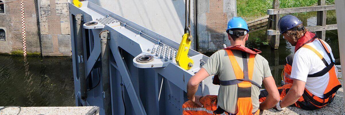 Twee monteurs werken aan een sluis