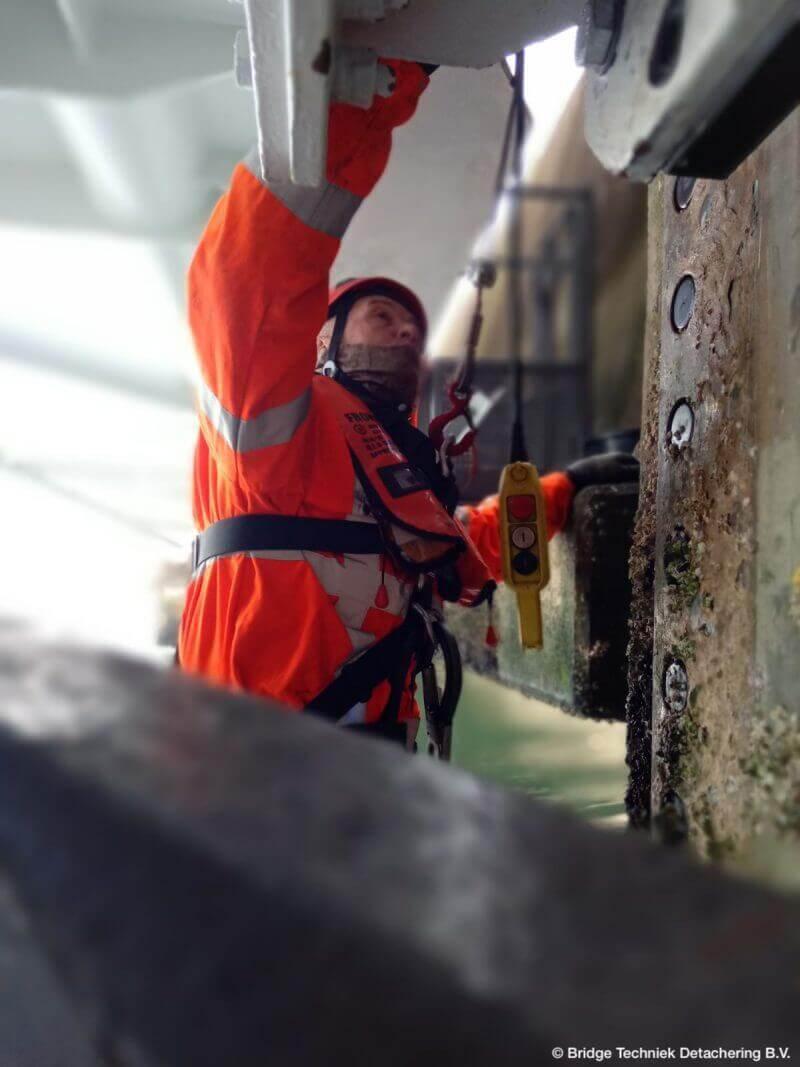 Monteur doet onderhoud aan een brug