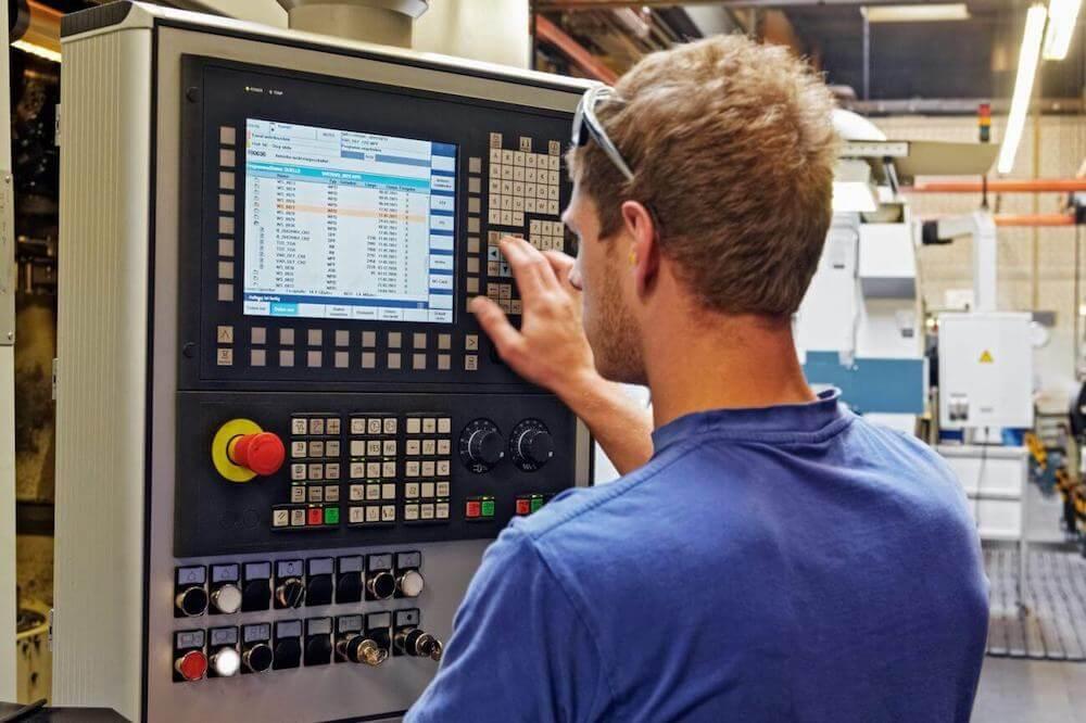 Verspaner bedient een CNC freesmachine